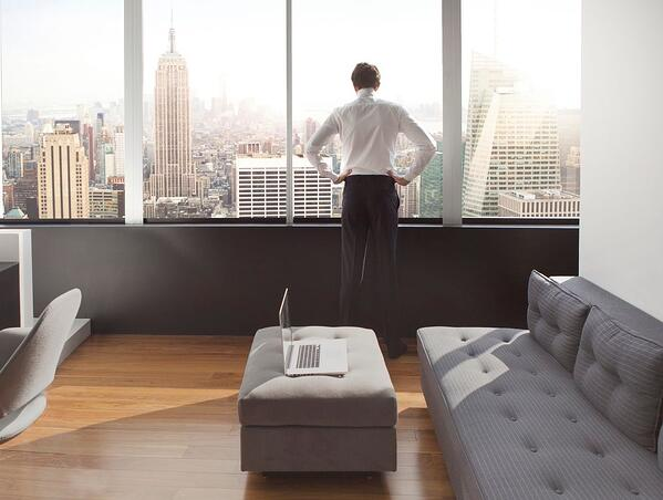 a young man in his luxury apartment looking out over the New York Skyline